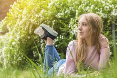 作梦在草的一个晴天的逗人喜爱的白肤金发的少年女孩 免版税库存照片
