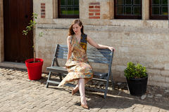 作梦在阳光下在长凳的女孩 免版税库存照片
