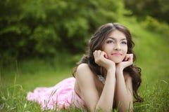 作梦在绿草的愉快的微笑的年轻新娘女孩在春天 免版税库存图片