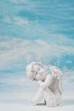 作梦或在蓝色天堂背景的哀伤的白色天使cond的 免版税库存照片