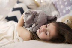 作梦逗人喜爱的愉快的拥抱她的玩具的小女孩睡觉和和床 关闭睡觉的孩子照片  图库摄影