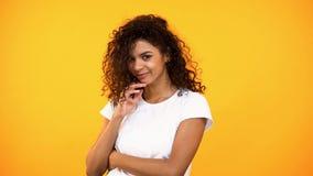作橙色背景的俏丽的年轻女人,做愿望,挥动,害羞的女性 库存图片