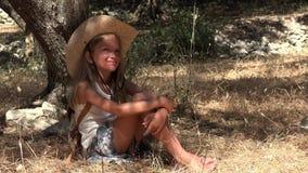 作由树的孩子在橄榄色的果树园,愉快的沉思女孩,冥想的孩子4K 股票录像