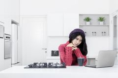 作白日梦与膝上型计算机的妇女在厨房里 免版税库存图片