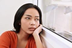 作白日梦和看通过窗口的亚裔妇女画象 免版税图库摄影
