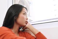 作白日梦和看通过窗口的亚裔妇女画象 图库摄影