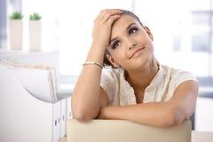 作白日梦在办公室的俏丽的妇女 免版税库存照片