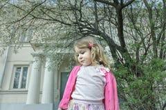 作白日梦的学龄前儿童女孩室外春天画象开花的果树和门廊背景的 免版税库存照片