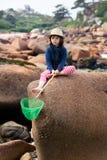 作白日梦的孩子不快乐或乏味坐花岗岩石头 免版税库存图片