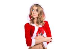 作红色圣诞老人的想法的愉快的沉思beautyful妇女穿衣 图库摄影
