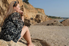 作美丽的女孩坐大石头 库存图片