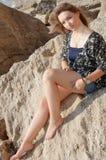 作美丽的女孩坐大石头 免版税图库摄影