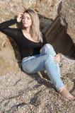 作美丽的女孩坐大石头 免版税库存图片