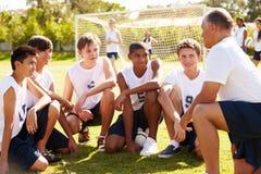 作队报告的教练男性高中足球队员 免版税库存照片