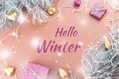 你好冬天与杉树、紫色giftboxes、金黄装饰品和圣诞灯的贺卡在棕色背景中 免版税图库摄影