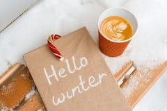 你好冬天,多雪的背景,圣诞节candi藤茎,咖啡,冬天书 免版税库存图片