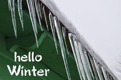 你好冬天 在一个绿色木房子的屋顶的冰柱 冬天季节概念 免版税库存图片