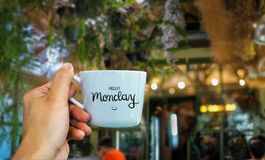 你好在举行在咖啡馆的咖啡杯手上的星期一文本 库存照片