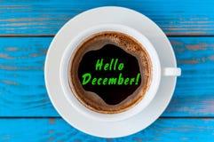 你好在咖啡杯写的12月在蓝色木书桌 伊芙、圣诞节和新年计时概念 图库摄影