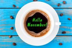 你好在咖啡杯写的11月在蓝色木表面 秋天时间概念,顶视图 库存照片