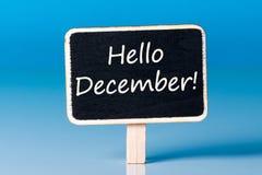 你好在标志的12月在蓝色背景 12月1日,圣诞节和新年假日和销售的起点 库存图片