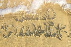 你好在海滩沙子用手写的夏天文本冲走由泡沫似的海波浪 顶视图 激动人心的生活方式图象 库存照片