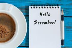 你好在笔记薄写的12月在早晨咖啡杯附近在经理或自由职业者工作场所 伊芙,圣诞节和新 图库摄影