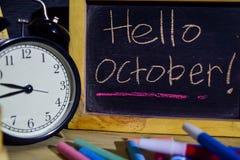 你好在词组五颜六色手写的10月在黑板 免版税库存照片