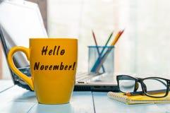 你好在黄色早晨咖啡杯或营业所工作场所背景在家写的11月 秋天时间概念 库存照片