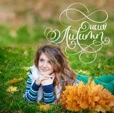 你好秋天书法字法文本 年轻美丽的女孩在有黄色花圈的秋天公园在头离开 免版税库存图片