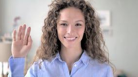 你好,欢迎的卷发妇女挥动的手
