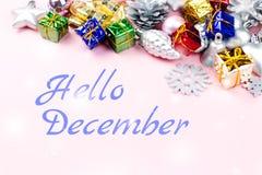 你好12月与五颜六色的圣诞节装饰品,礼物的贺卡在背景中 免版税库存图片