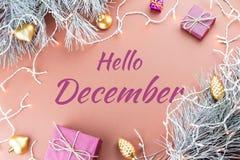 你好12月与杉树、紫色giftboxes、金黄装饰品和圣诞灯的贺卡在棕色背景中 免版税库存图片