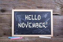 你好11月!与纹理和白垩bla的老木背景 库存照片