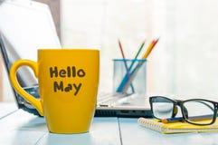 你好5月-发短信在黄色有膝上型计算机的咖啡杯在营业所背景,工作场所和玻璃 春天…上升了叶子,自然本底 免版税库存图片