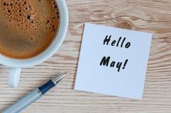 你好5月-在木纹理背景的消息与早晨咖啡杯 国际劳动节假日概念 免版税库存照片
