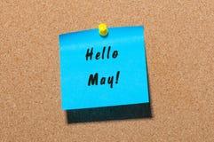 你好5月-在蓝色贴纸的消息被别住在黄柏布告牌 背景概念花春天空白黄色年轻人 免版税库存照片