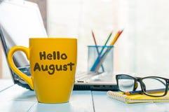 你好8月-在黄色早晨咖啡或茶杯的题字在营业所背景 夏天月,日历 库存图片