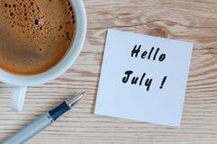 你好7月-消息在家或办公桌 使用早晨咖啡 这里概念夏天 免版税库存图片