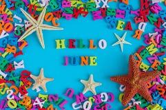 你好6月-词组成由小色的信件在与海滩属性的蓝色背景-海星或五手指 免版税库存图片