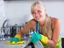 年轻佣人打扫灰尘厨房上面 免版税库存照片