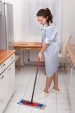 年轻佣人清洁厨房地板 免版税库存照片