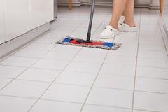 年轻佣人清洁厨房地板 库存照片