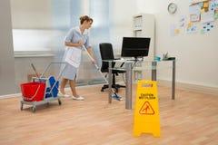 佣人清洁地板在办公室 免版税库存图片