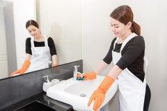年轻佣人清洁水槽在卫生间,面孔在墙壁镜子,清洁服务概念反射了 免版税库存图片