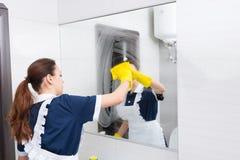 佣人清洗的被抹上的镜子 库存照片