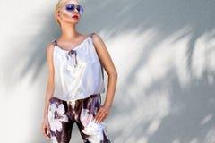 佩带一个典雅的衣服和高跟鞋和太阳镜立场的美丽的现象惊人的典雅的豪华性感的白肤金发的式样妇女 免版税库存照片