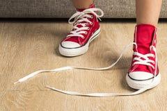 佩带一个对红色运动鞋的女孩 免版税库存照片