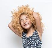 佩带一个白肤金发的假发和滑稽的表情亚洲人女孩 库存图片