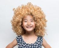 佩带一个白肤金发的假发和滑稽的表情亚洲人女孩 图库摄影